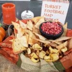 Cranberry Apple Jalapeno Salsa in a black salsa dish with with homemade cinnamon sugar tortilla chips in a decorative fall napkin and a sign that says Turkey, Football, Nap, Repeat