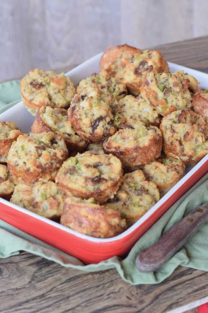 Individual size sausage cornbread dressings baked in a muffin pan and  piled up in a red deep platter on a green cloth