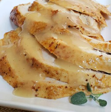 Slices of turkey breast with skin on overlapping each other on a white plate and garnished with fresh sage and gravy poured over the turkey slices