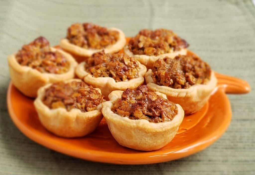 Seven Maple Pecan Tassies on an orange pumpkin shaped plate