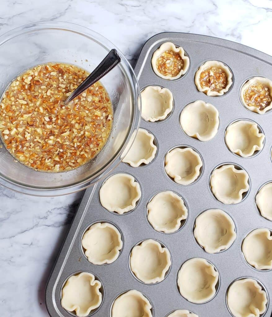 Rounds of refrigerated pie dough fitted in mini muffin pans with a bowl of Maple Pecan Pie filling next to it.