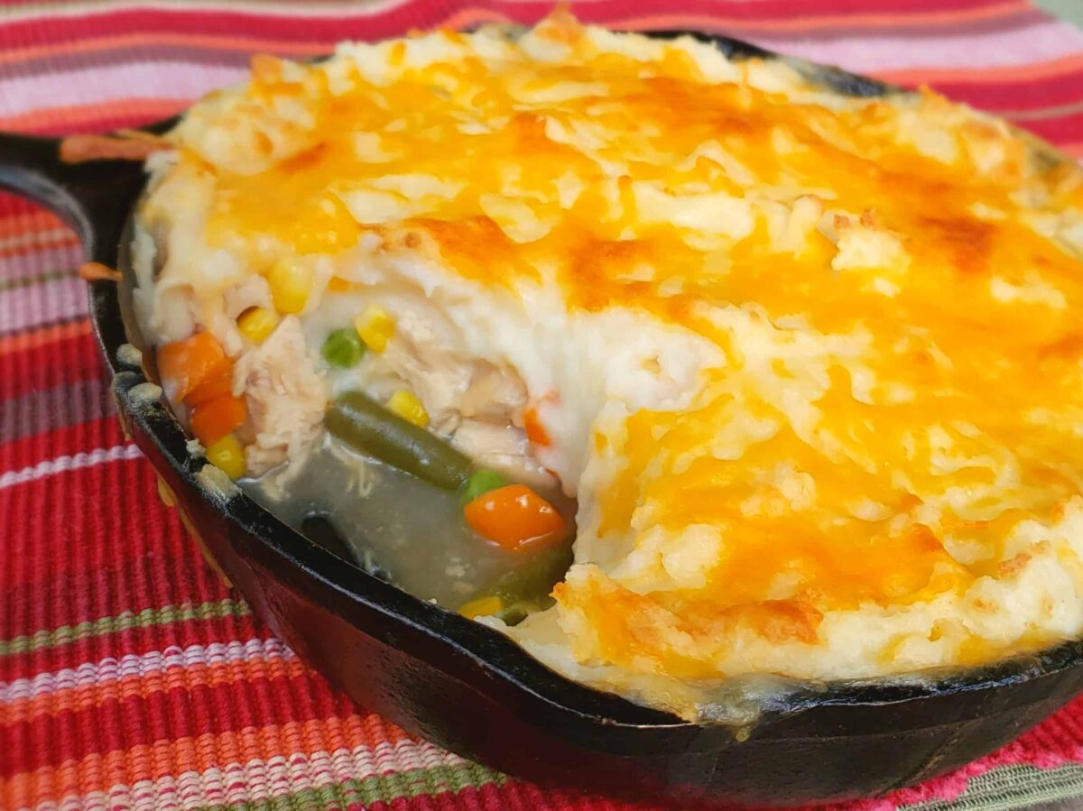 Shepherds Pie made with leftover Thanksgiving turkey vegetables and gravy. Made in a cast iron skillet with multi colored cloth.