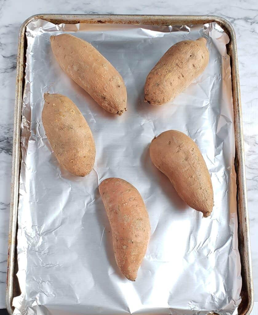 5 sweet potatoes on a foil-lined baking sheet