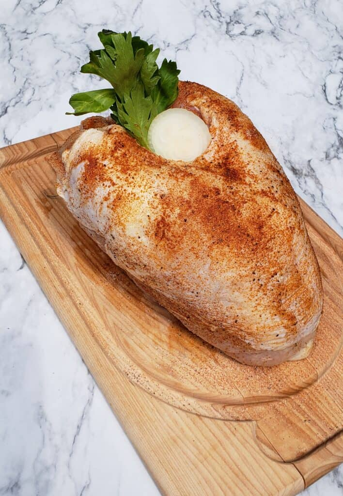 Uncooked turkey breast on a wooden cutting board stuffed with celery leaves and onion on a marble surface
