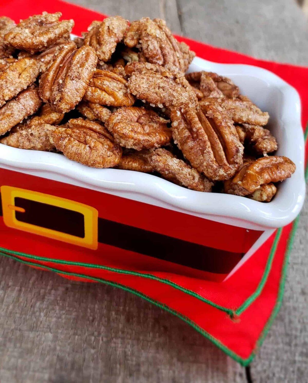 Cinnamon Sugar Pecans in a Santa belt rectangle dish