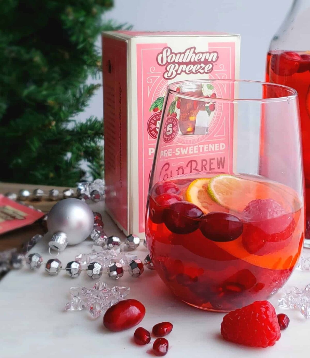 stemless wine class of sangria with pink box of tea and sliver Christmas beads on white surface