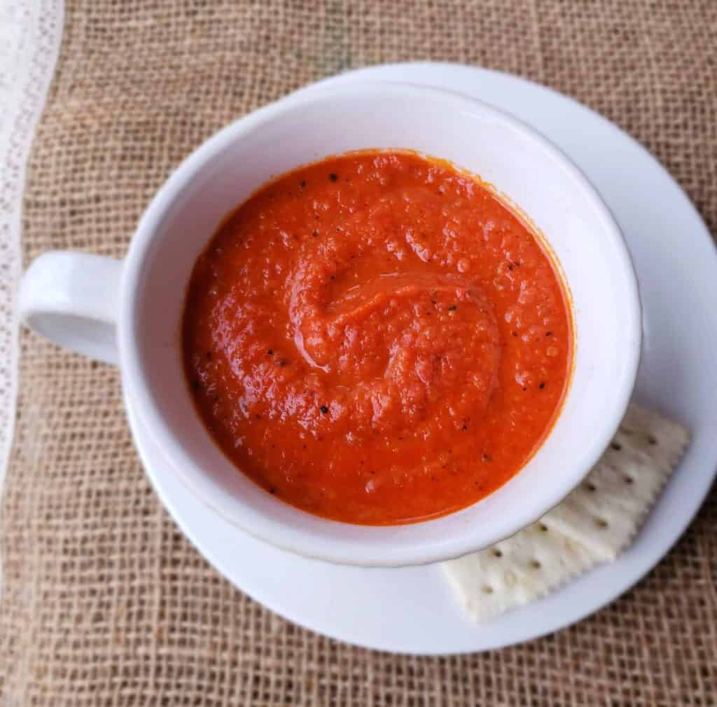 This shortcut version of Pappa al Popodoro is made with cans of fire-roasted tomatoes and thickened with bread. and served in a white soup cup on burlap surface.