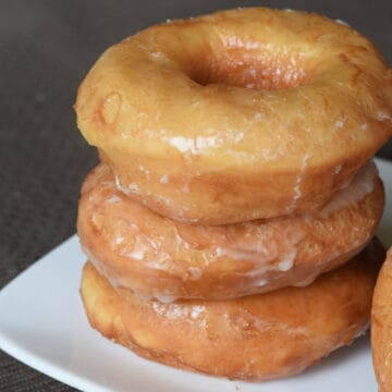 Stack of 3 glazed yeast donuts on a white plate