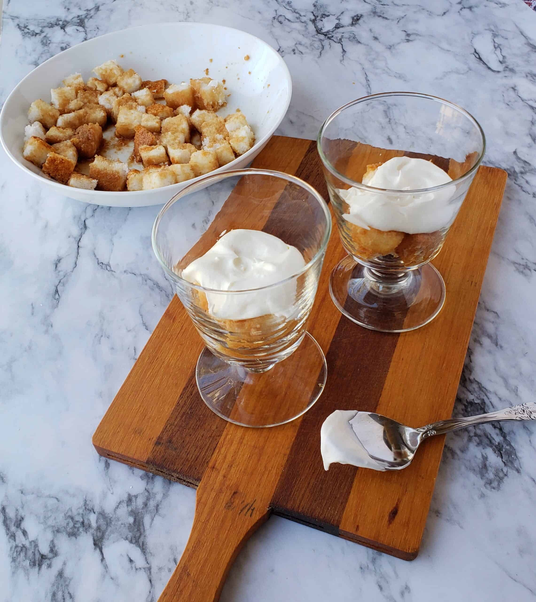 Layer sweet tea soaked cake cubes in small dessert dishescreamy Neufchatel mixture on wooden cutting board
