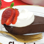 Slice of chocolate tart on white plate topped with whipped cream and a fanned strawberry; gold fork on the plate