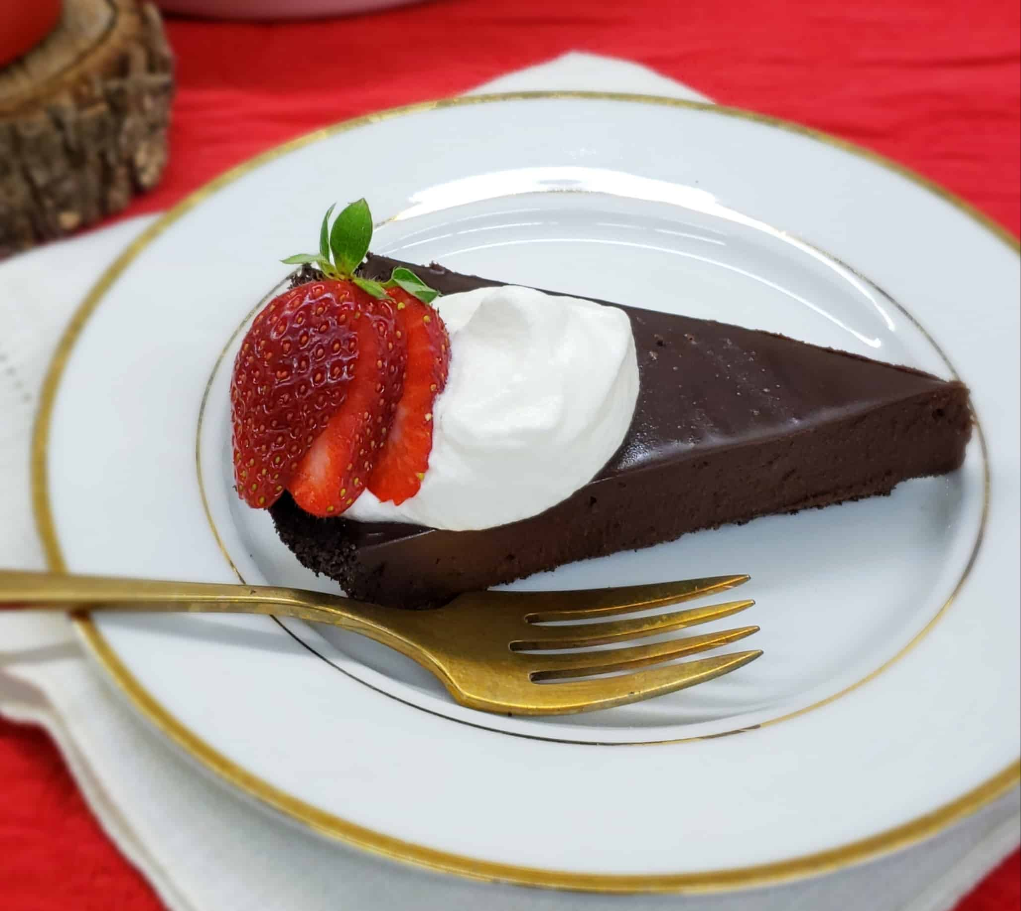 Slice of chocolate tart with whipped cream and strawberry slices on a gold rimmed plate and gold fork