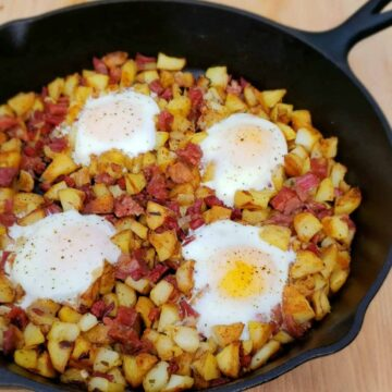 cast iron skillet of corned beef hash with shirred eggs