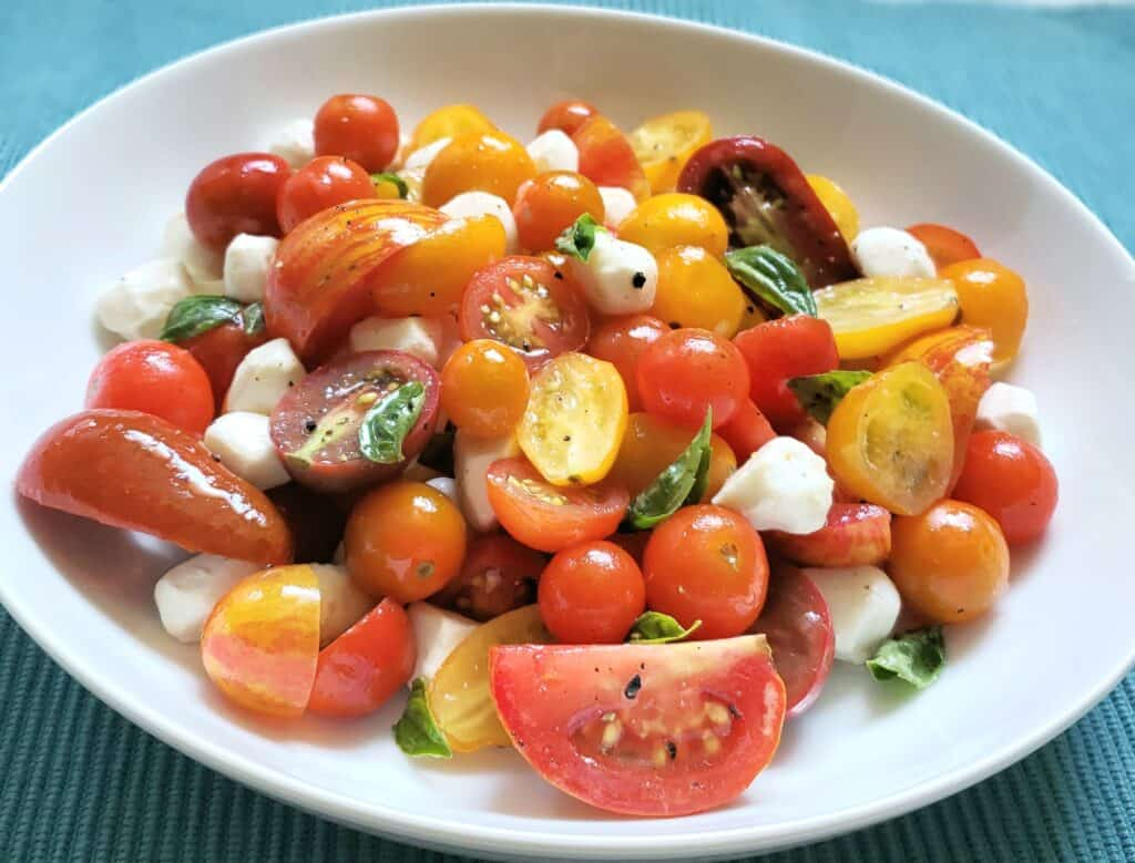 Tossed Caprese Salad is simply multi colored grape and tear drop tomatoes, pearl mozzarella, and basil tossed in Italian or lemon salad dressing