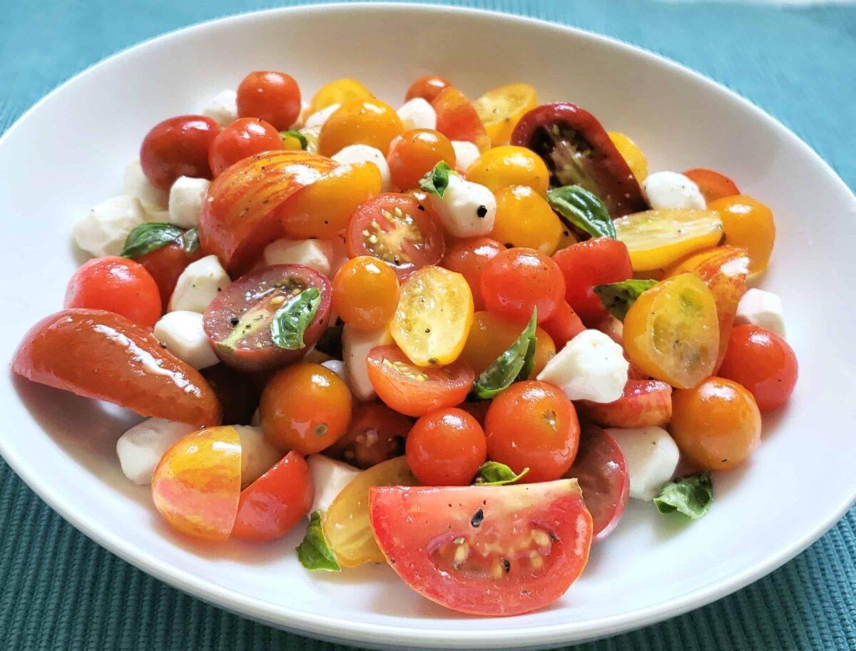 multi colored grape and tear drop tomatoes, pearl mozzarella, and basil in a white bowl