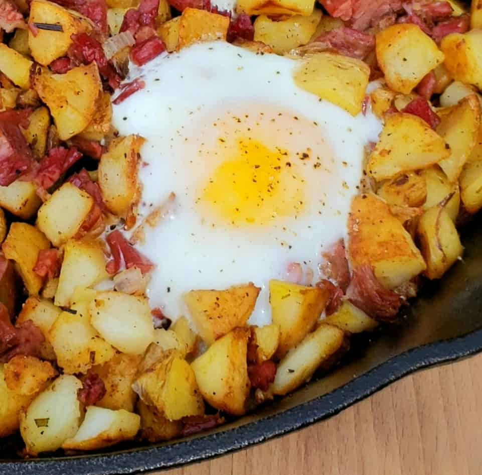 Crack an egg right into each hole in the corned beef hash. Cook over medium heat until the bottom of the egg is starting to become opaque-about 1 minute. Then, place the skillet under the broiler in your oven about 3 inches from the broiler. Broil 30 seconds to 1 minute, depending on how you like your eggs cooked.