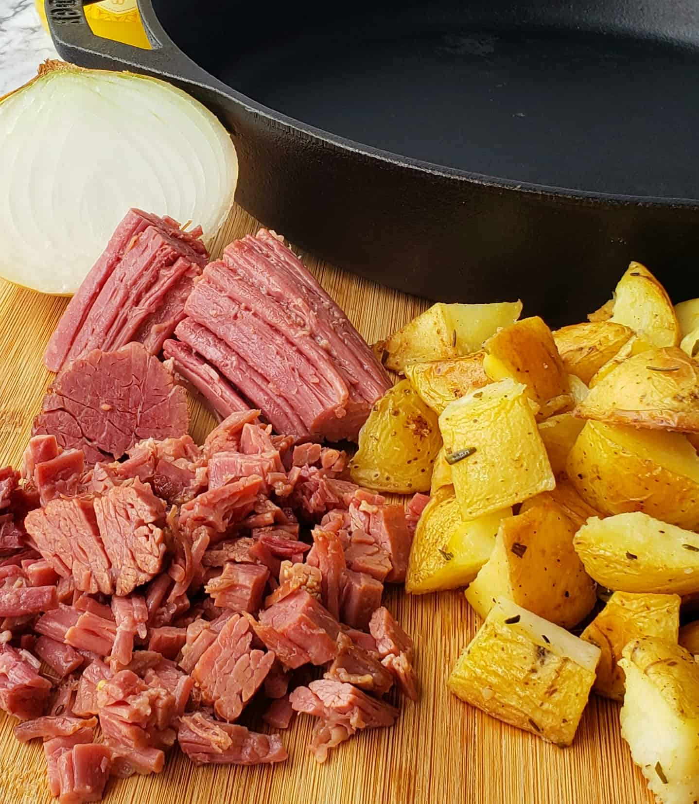 chopped corned beef, half an onion and roasted potatoes next to a cast iron skillet