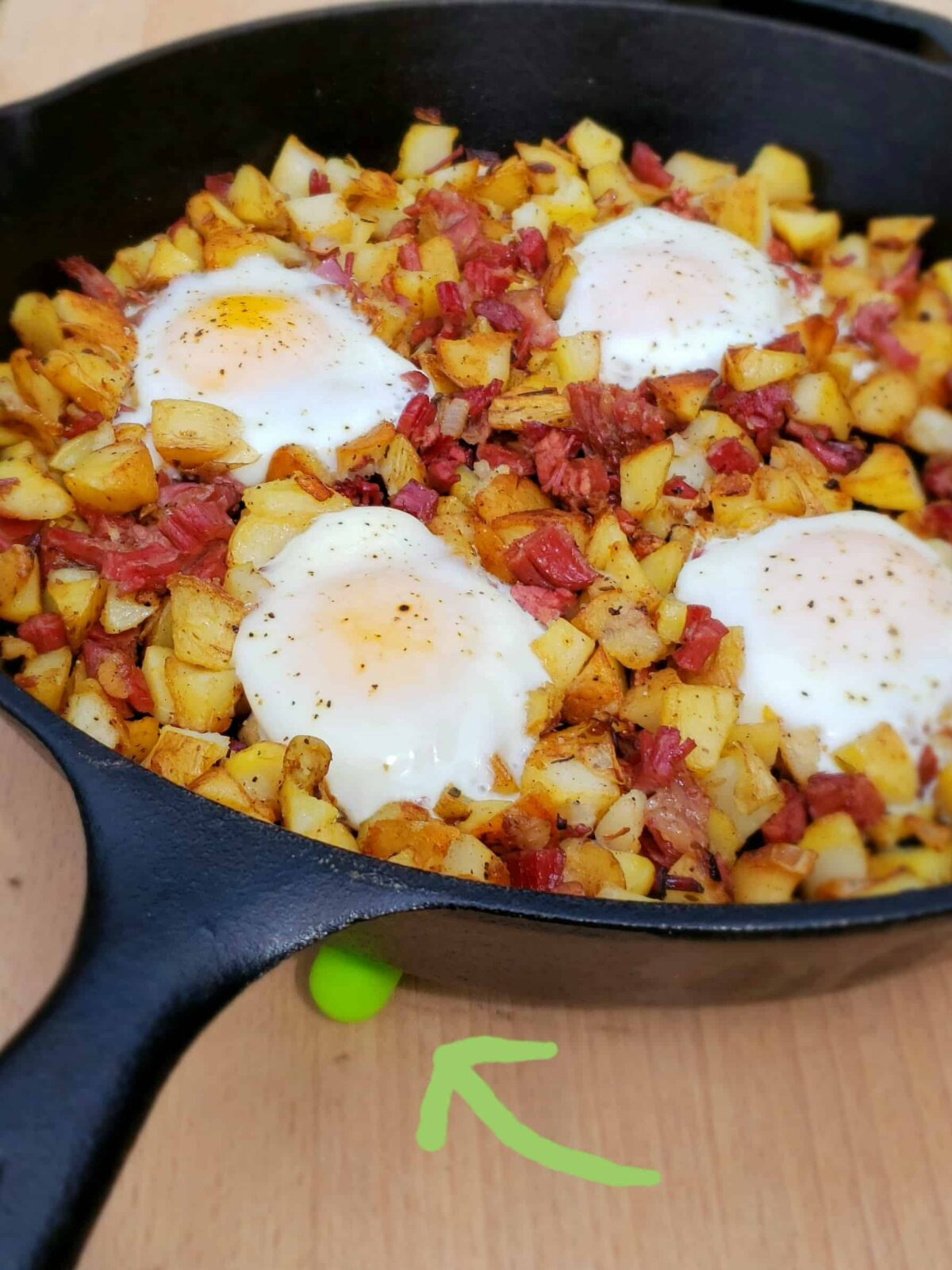 corned beef hash with shirred eggs; green arrow pointing to green trivet