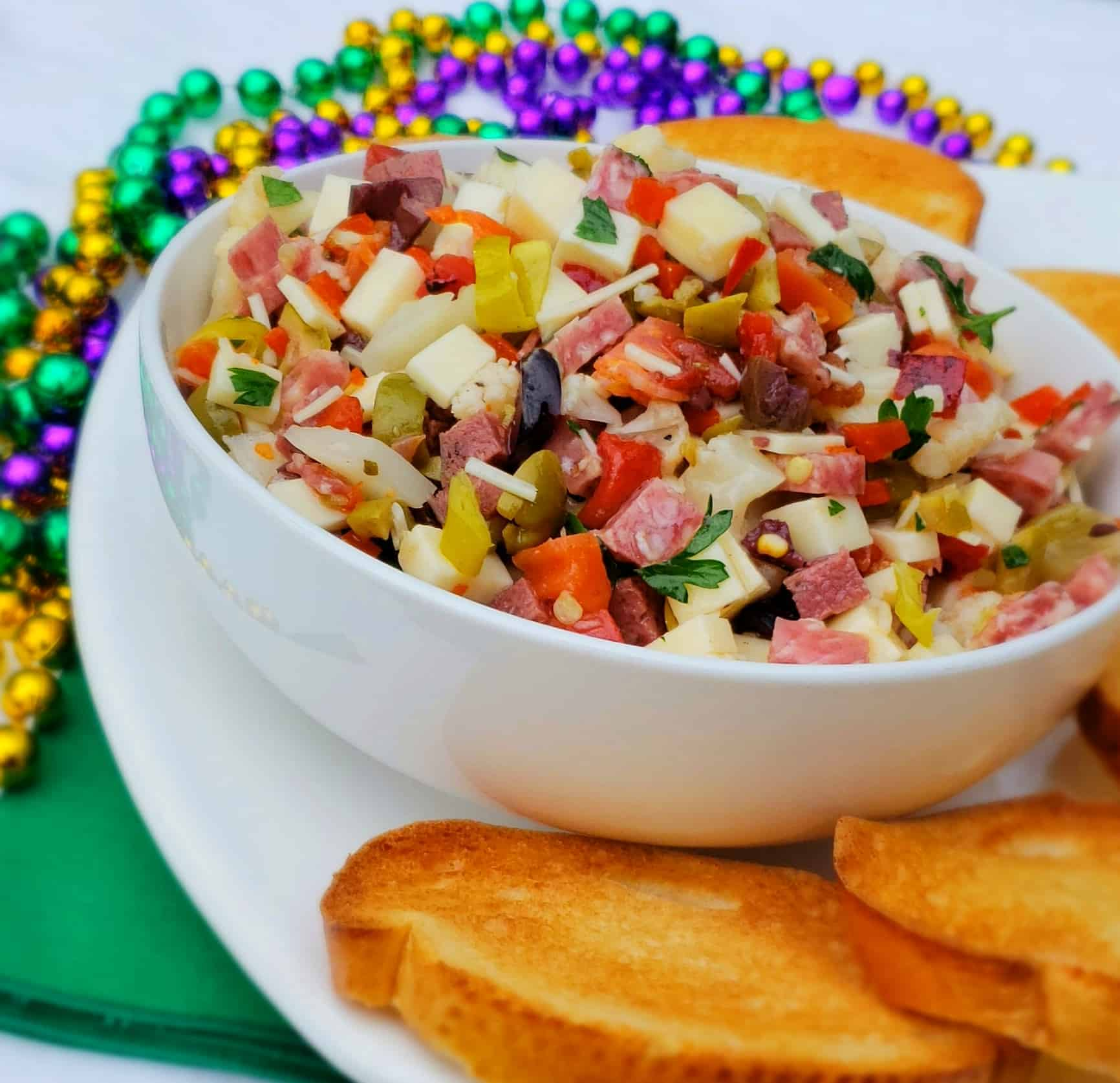 chopped meats and cheeses in a white bowl with mardi gra beads