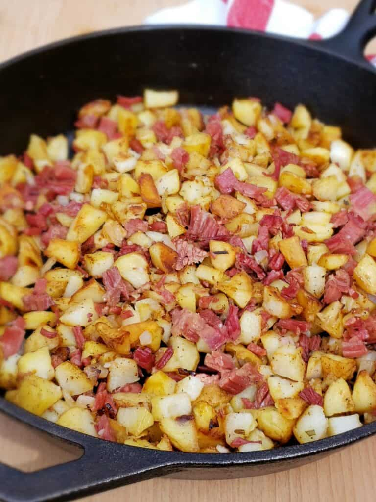 Since the corned beef is already cooked, you are just heating it up in the skillet with the potatoes. Turn the heat back down to medium. Add salt and pepper and cook, stirring occasionally, just until heated.