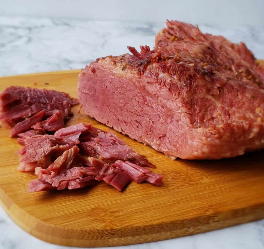 Slice the corned beef brisket diagonally against the grain. Otherwise, you will have long strings of meat. You can also shred the meat before or after slicing it by pulling it apart with two forks.