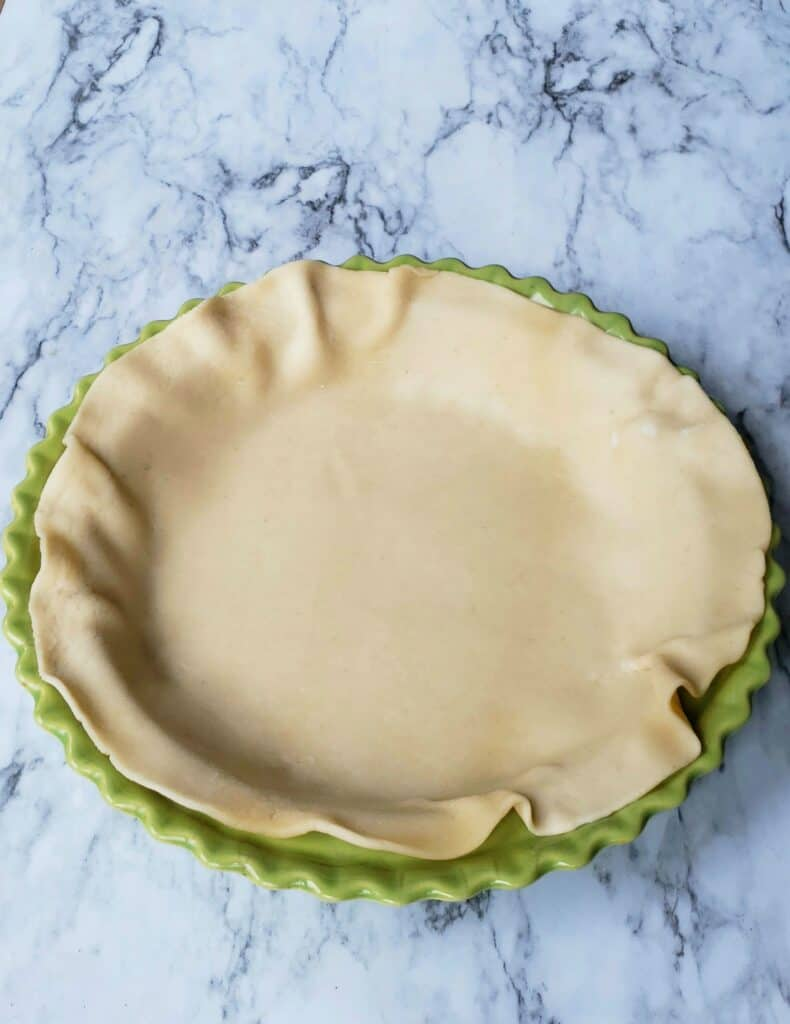 Fit the refrigerated pie crust into the bottom of a 9-inch pie plate. Don't press the crust too firmly or it will stick. Don't stretch and pull it either. Place it in the refrigerator while you combine the filling.