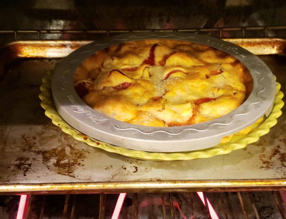 Strawberry Rhubarb Pie with a pie crust shield around the edges