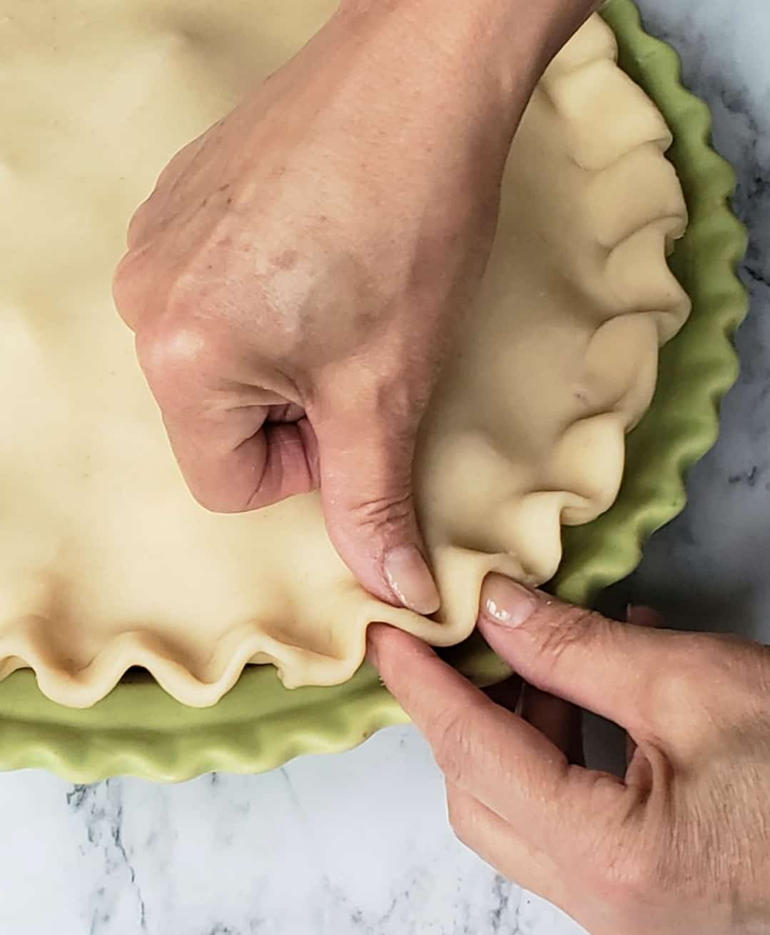 Crimping pie dough with thumb and finger in a green fluted pie dish
