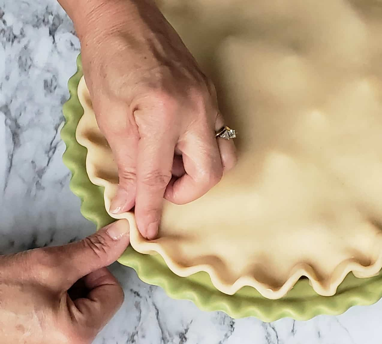 Crimping pie dough edges with thumb and finger
