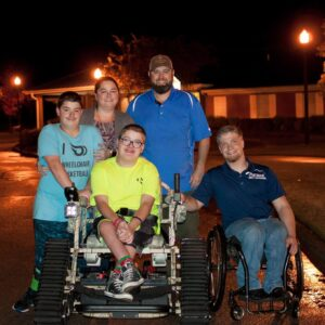 In 2018 Outdoor Ability Foundation presented brothers with spina bifida an Action Track Chair. Seen here with parents and Grayson Phillips.