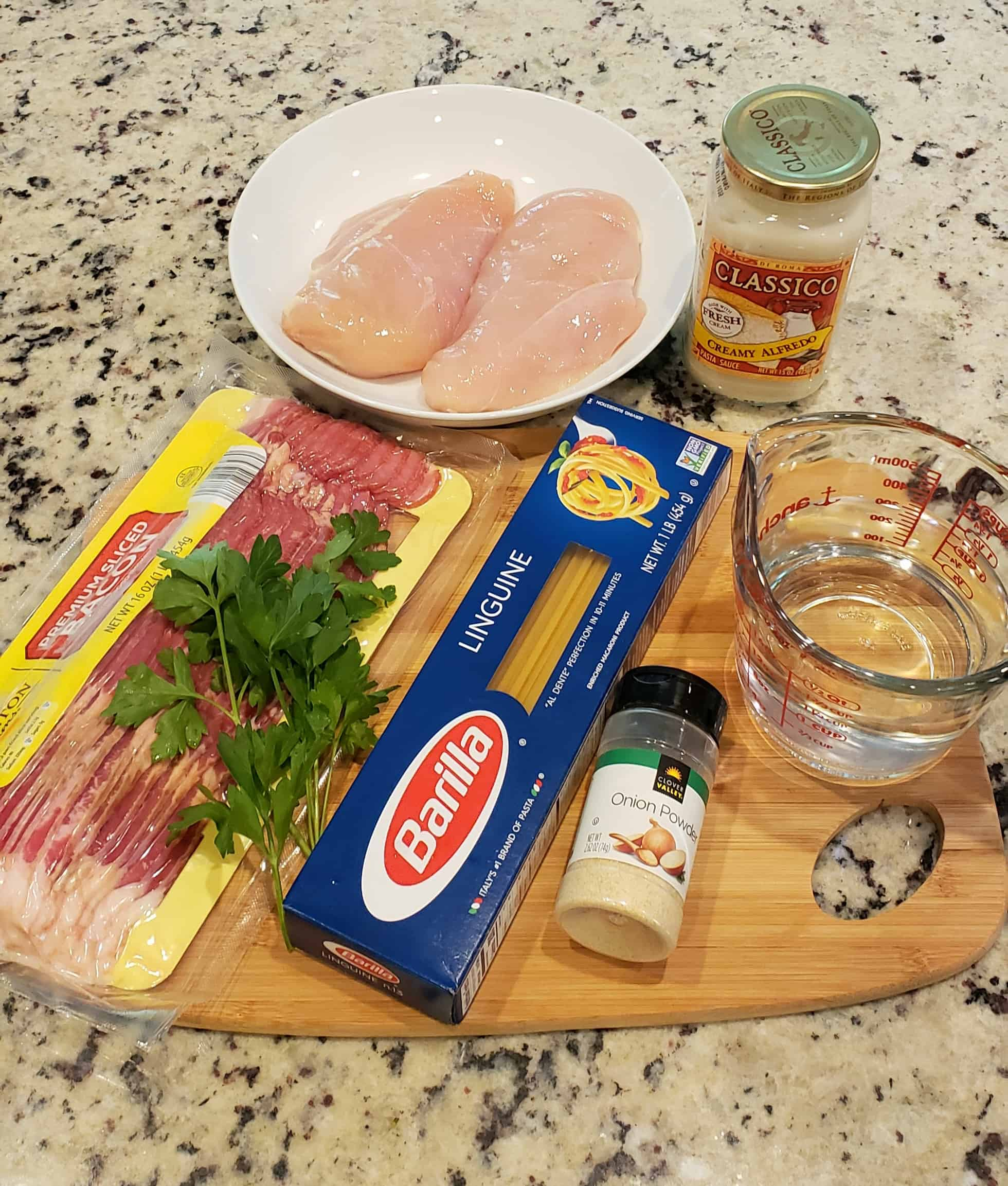 Ingredients on a wooden cutting board: chicken breasts, bacon, parsley, linguine, alfredo sauce, garlic powder water