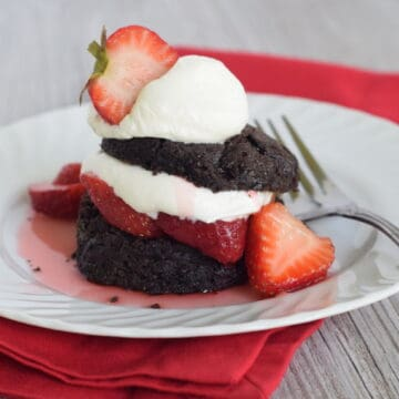 Chocolate biscuits layered with strawberries and whipped cream on a white plate