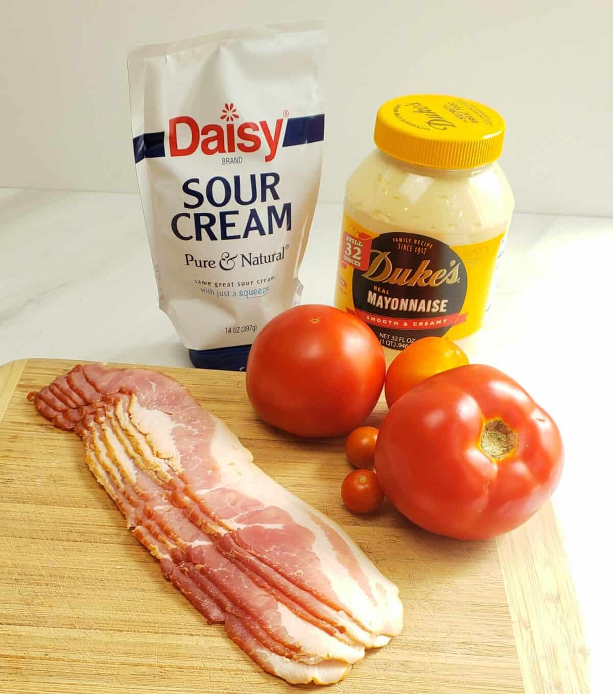 Ingredients on a wooden cutting board: sour cream, Dukes mayonnaise, uncooked bacon, tomatoes