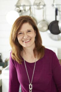Kathleen Royal Phillips, author of food blog GritsAndGouda.com with pots behind her