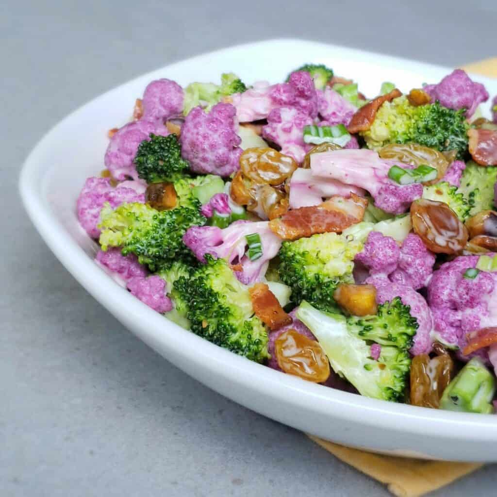 Salad in a white bowl on a yellow napkin. Salad ingredients: purple cauliflower, broccoli, golden raisins, pistachios and bacon