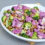 White rimmed plate of purple cauliflower and broccoli salad