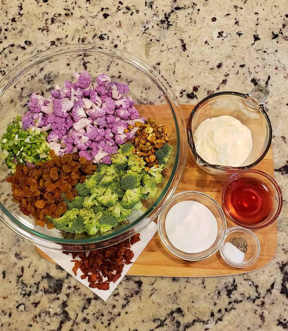 Ingredients in a glass bowl red wine vinegar, Dukes mayonnaise, green onion, golden raisins, bacon, broccoli, purple cauliflower