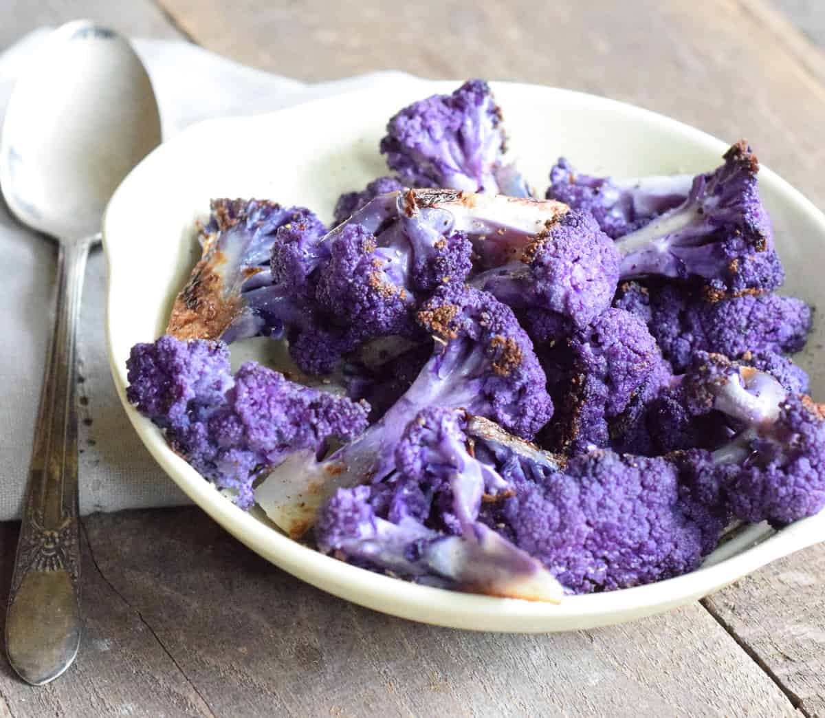 roasted purple cauliflower florets in a white bowl on a wooden surface