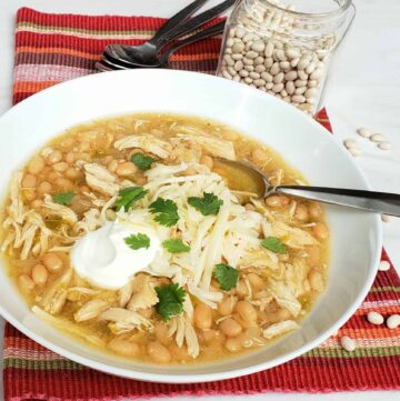 white bean chicken chili in white bowl on red cloth
