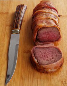 venison bacon wrapped tenderloin next to a knife