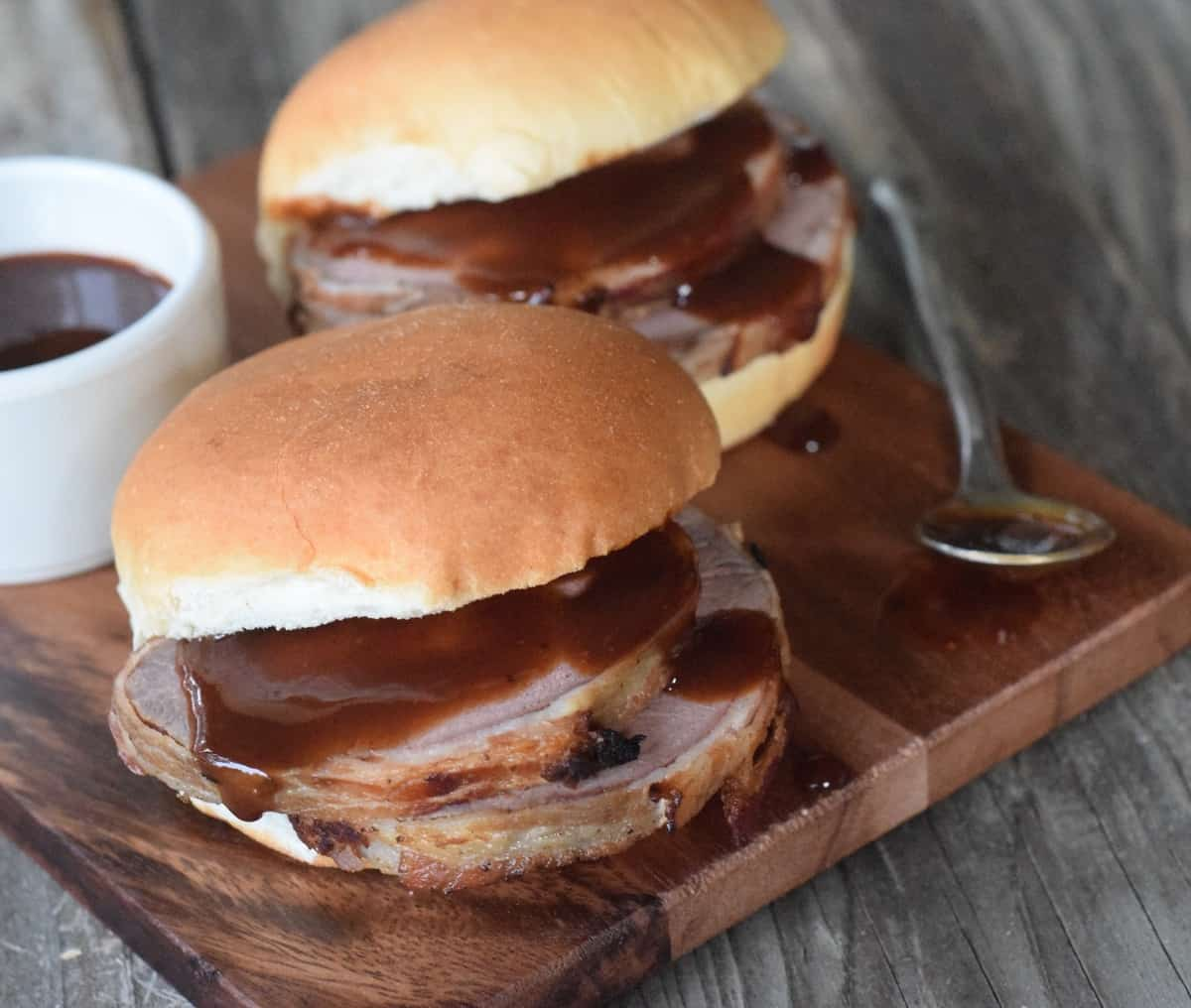 Two venison sliders on wooden cutting board with bbq sauce dripping