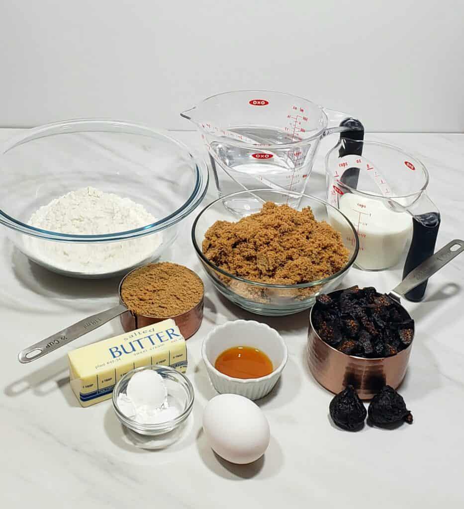 Ingredients to make a fig cake. flour, brown sugar, butter, baking powder, dried black figs, vanilla, milk water