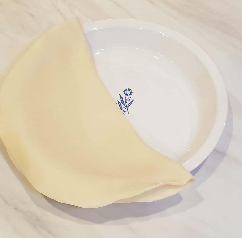 Peanut Pie unbaked pie dough folded in white Pyrex pie plate