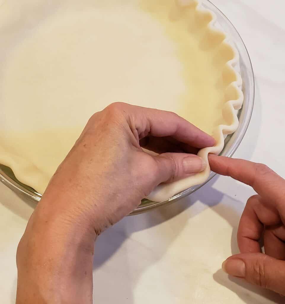 fluting pie crust with hands