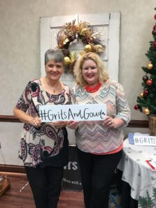 Guests holding up Grits and Gouda selfie signs at the Holiday Cooking Show