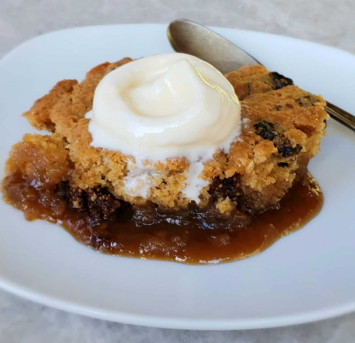 Mission fig cake with sauce scooped onto a white plate with ice cream