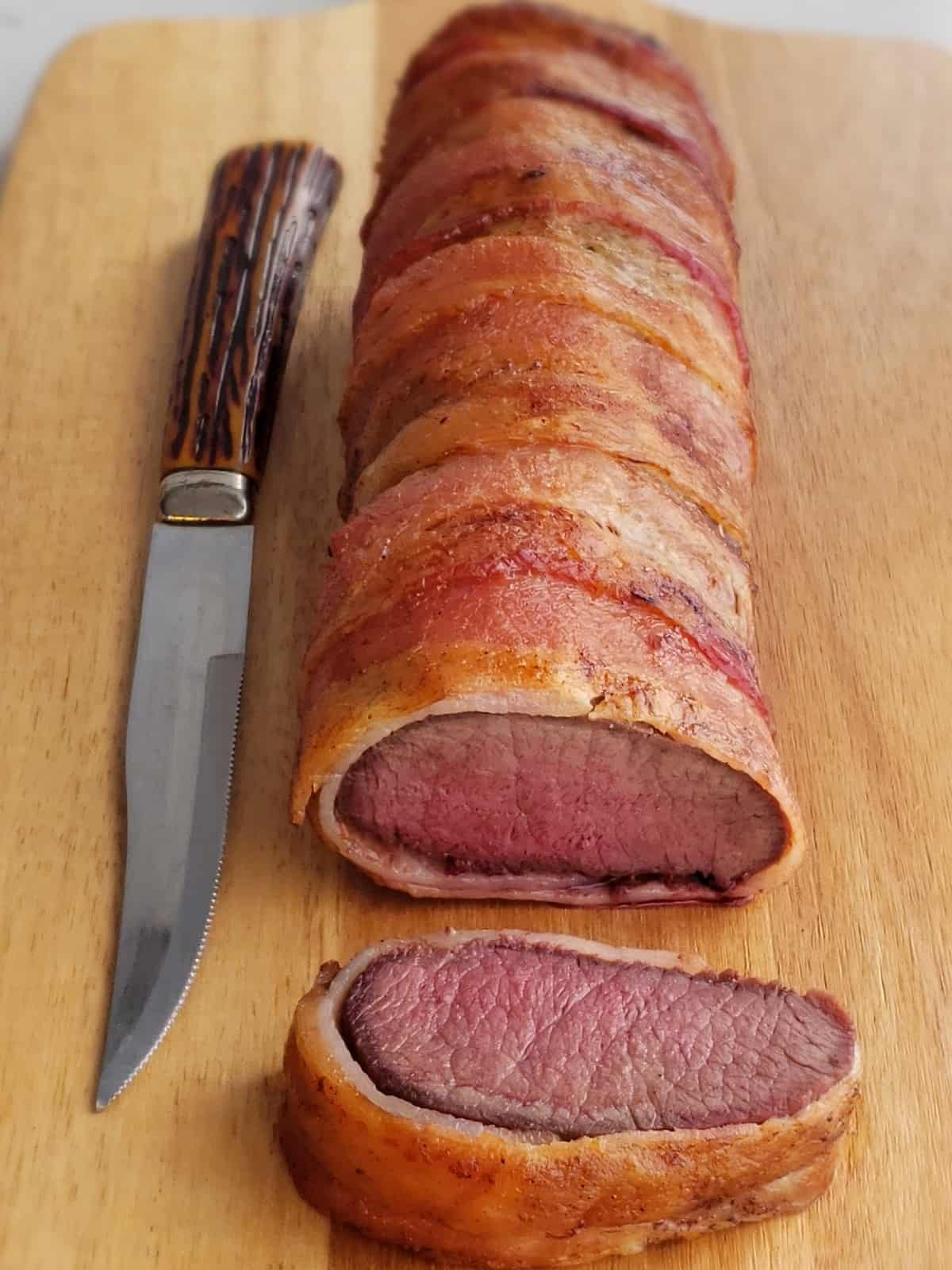 venison roast wrapped in bacon. slice on cutting board