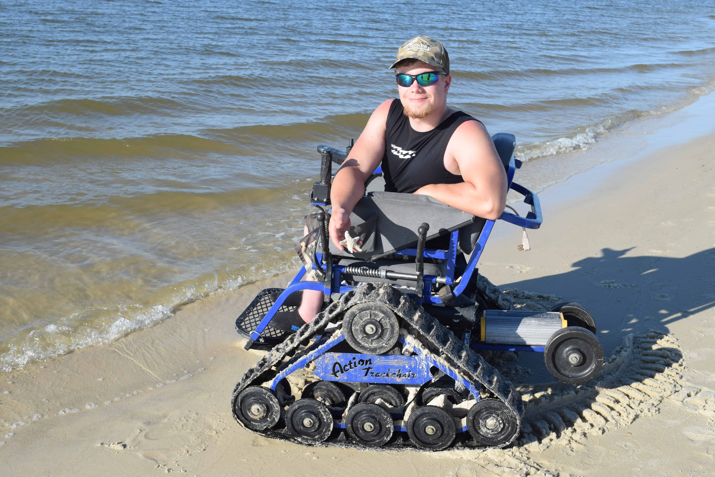 boy in all terrain power wheelchair holding star fish on beach