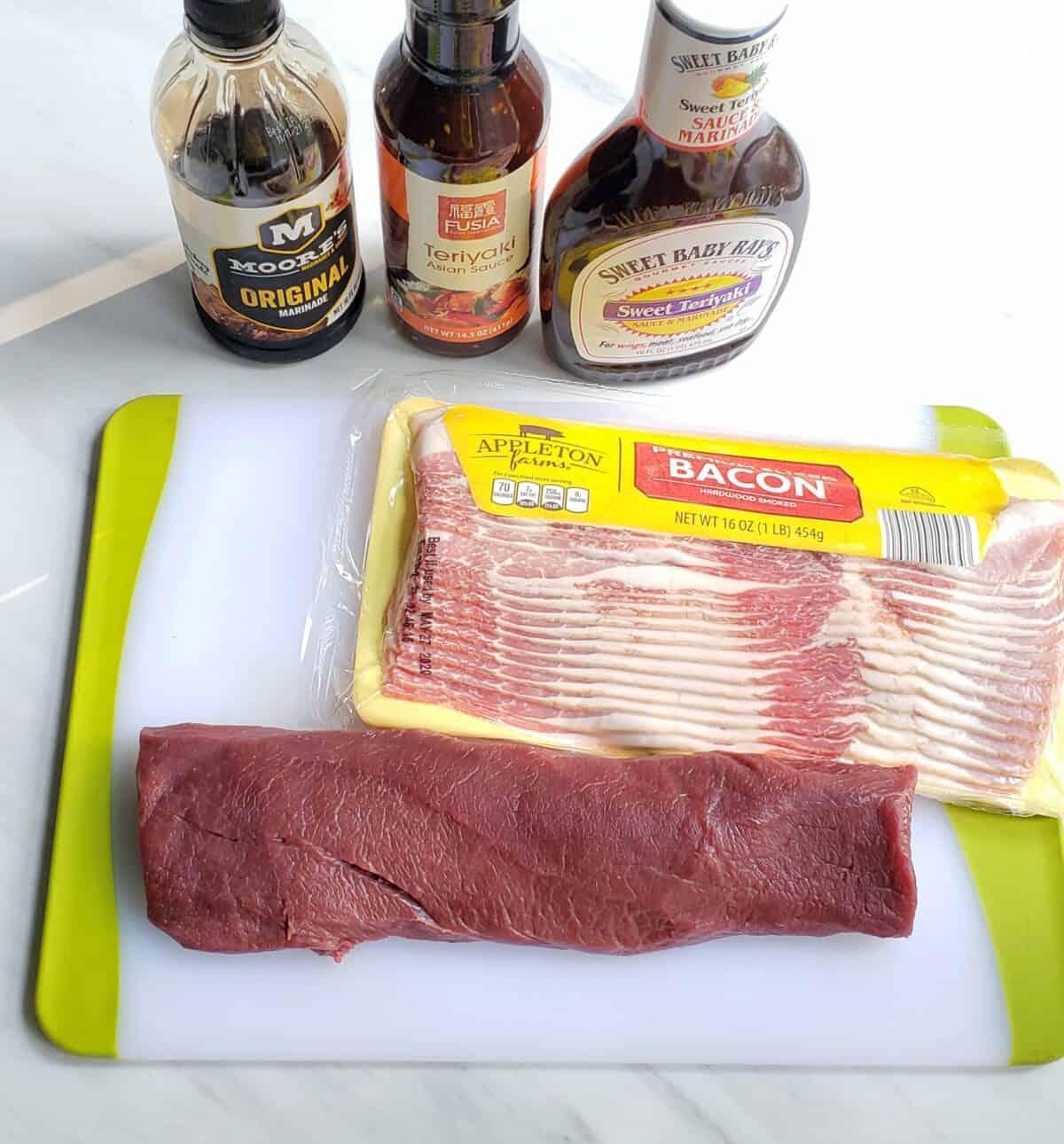 ingredients: bacon, venison roast, teriyaki sauce on a cutting board
