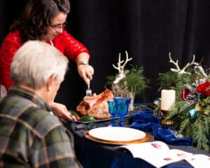 woman cutting ham for man sitting at table