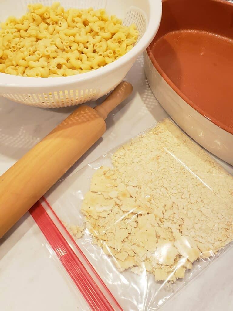 crushed saltine crackers in ziploc bag, rolling pin,